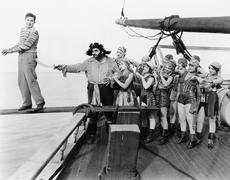 Group of pirates trying to push a young man over a plank Stock Photos