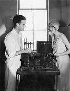 Woman smiling at a man next to an editing machine Stock Photos