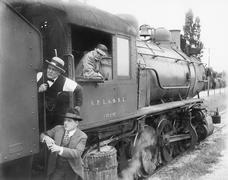 Three men waiting at a steam locomotive Stock Photos