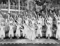 Group of dancers standing on a stage with their arms in the air and drinks Stock Photos