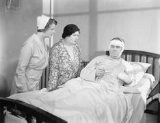 A wife next to her husband in a hospital bed with a nurse attending Stock Photos