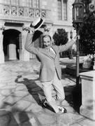 Mies tanssii kadulla heiluttaen hattu Kuvituskuvat