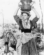 Young woman with water bucket on her head next to a well - stock photo