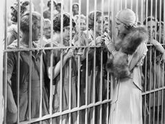 One woman standing in front of a jail talking with a group of women Stock Photos