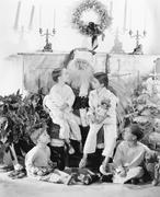 Santa Claus with presents and a group of children in front of a fire place Stock Photos