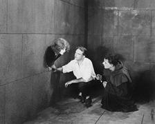 A priest and a man trying to help a young woman escape - stock photo