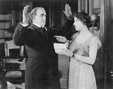 Woman with a letter in her hand pointing at a man - stock photo