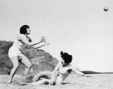 Two women playing with a ball at the beach Stock Photos