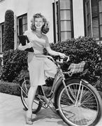Woman sitting on her bicycle with a book in her arms Stock Photos