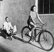 Woman on a bicycle pulling a grown man on a toy tricycle Stock Photos
