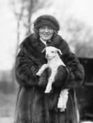 Woman in a fur coat and hat holding a small baby lamb in her arms - stock photo