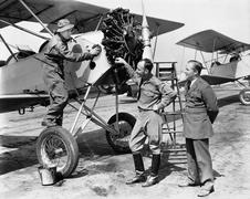 Three men standing next to an aircraft having a conversation - stock photo