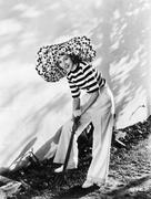 Woman with oversized hat digging in the garden Stock Photos