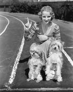Woman with her two dogs on a race track - stock photo