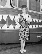 Female conductor standing in front of a tour trolley - stock photo