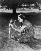 Woman kneeling on the lawn playing with a tame raccoon - stock photo