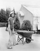 Woman walking with a wheel barrel Stock Photos