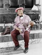 Shoeshine man working and smiling Stock Photos
