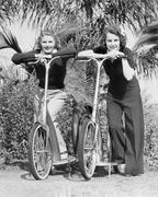 Two women standing on their scooters Stock Photos