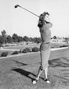 Woman on the driving range swinging a golf club Stock Photos