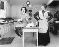 Housekeeper in the kitchen glaring at a young woman eating a cake Stock Photos