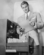 Liikemies katsot paperia vieressä arkistokaappi Kuvituskuvat