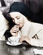 Nun sipping tea out of a teacup with a straw Stock Photos