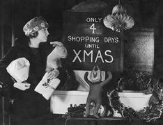 Woman reading sign with number of shopping days until Christmas - stock photo