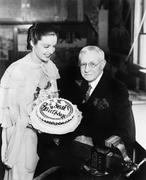 Young woman presenting a birthday cake to an elderly man Stock Photos