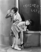 Teacher spanking a girl in a classroom Stock Photos
