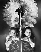 Two children sitting under a wreath holding a Christmas story book Stock Photos