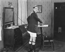 Man in sock garters ironing - stock photo