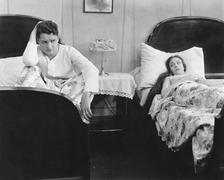 Young couple in separate beds after fight - stock photo