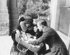 Happy family looking at new born baby - stock photo