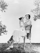 Elegant woman sitting on chair while holding binoculars Stock Photos