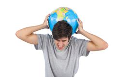Man suffering because of a globe - stock photo