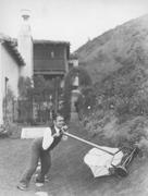 Man struggling to mow lawn - stock photo