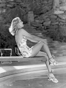 Smiling woman sitting on edge of diving board Stock Photos