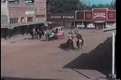 Horse drawn carriage riding through western town Stock Footage