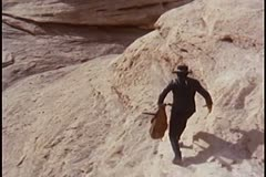 Rear view of man running down rocky mountain Stock Footage