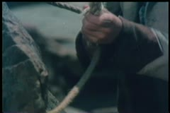 Medium shot of man tying rope around rock Stock Footage
