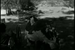 Men in cowhide costume running towards real herd of cows Stock Footage