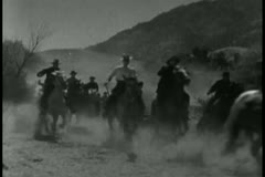 cowboys on horseback galloping across prairie - stock footage