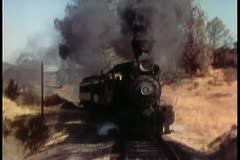 Front view of vintage steam locomotive passing through countryside Stock Footage
