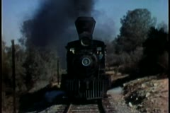vintage steam locomotive passing through countryside - stock footage