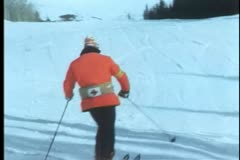 Rear view of ski patrol skiing down slope Stock Footage