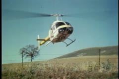 Helicopter equipped with film camera landing in field Stock Footage