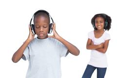 Little boy with eyes closed listening to music with his sister - stock photo
