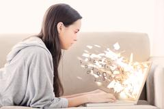 Woman using laptop with binary codes exploding over - stock photo