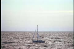 Wide shot of a sailboat drifting on an open ocean Stock Footage